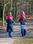 Eltern tragen ihre Kinder auf der Schulter. Eine Alternative ist die Kindertrage.